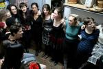 Slavs and alumnae gather in a closet full of baskets to sing together at Golden Fest